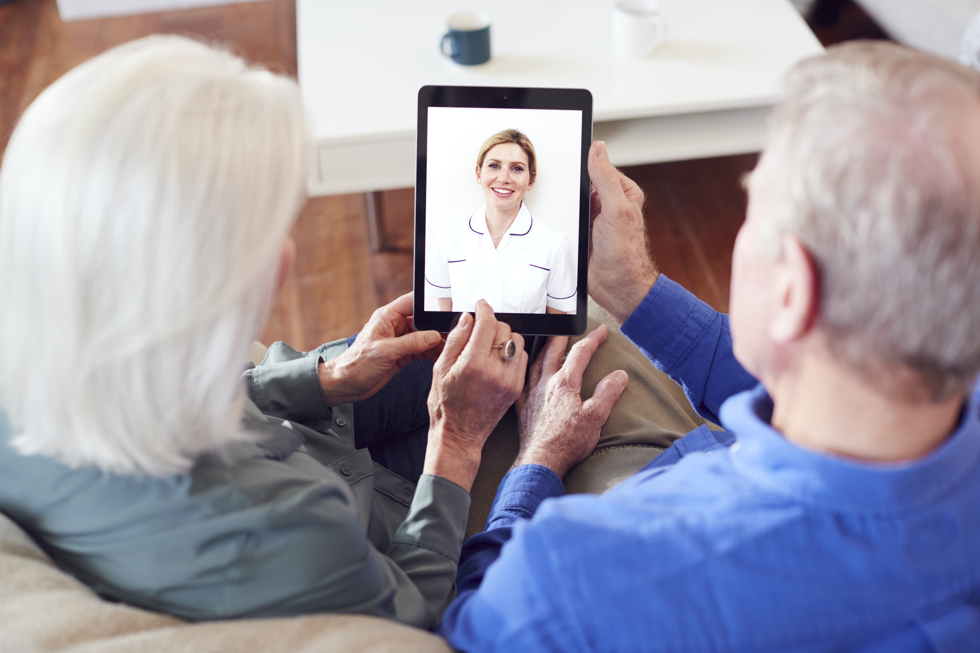 Female Doctor Having Video Consultation With Senior Couple On Digital Tablet At Home